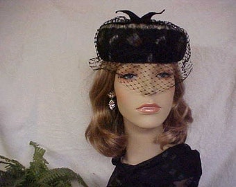 Black pill box hat with diamond face veil and feathers under netting and has union label- fits 22 inches
