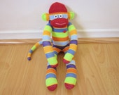 80s striped sock monkey plush with neon green, red, blue, and orange stripes