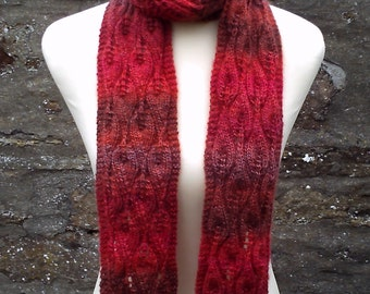 Hand knitted lacy self patterning skinny scarf . Adult women or teenage girls. Red and orange tones.