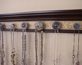 "Brown jewelry organizer. This necklace wall rack has 7 decorative cabinet knobs neutral colorson embossed background 20 "" jewelry storage"