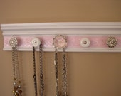 Jewelry organizer. This wall rack necklace hanger has a white background & metallic soft pink embossed center 5 knobs total 15 ""