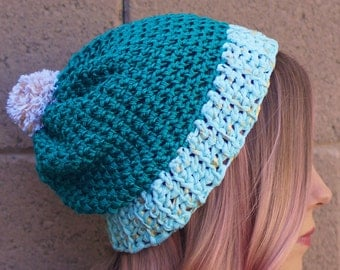 turquoise beanie with gold accents and a pom pom
