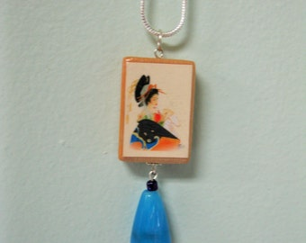 "Decoupaged Catalin "" Joker "" pendant with matching blue bead"