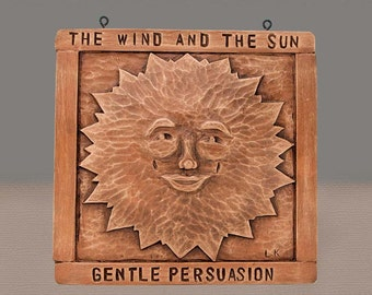 Sun plaque in antique bronze.  Illustrating the Aesop's fable 'The Wind and the Sun'