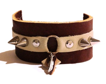 Brown and tan leather cuff bracelet with spikes and feather charm