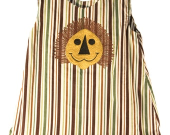 Embroidered  jumper with smiling lion face and ruffle at the bottom of the skirt.
