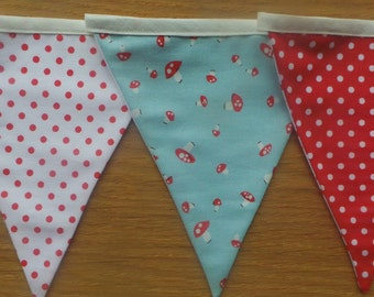 Bunting in aqua, red and white toadstool fabric and red and white polka dot fabric with 9 flags