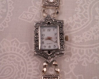 Beautiful Watch/Bracelet with silver tone crystals and silver tone accents and watch face and magnetic silver fold-over clasp