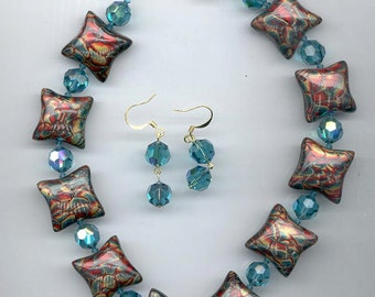 Necklace and earrings showcasing amazing polymer clay beads by Elsie Smith in shimmering red, teal, and gold