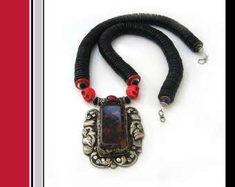 Prospero: Antique Tibetan amber and silver pendant with red skulls. Necklace and earring set.