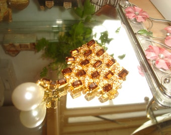 A gold effect gradation with 15 topaz effect stones brooch, witha drop pearl