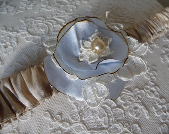 Silk garter with a blue/ivory flower corsage, Dolly