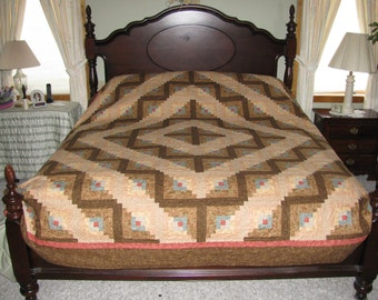 King size quilt of tans, browns,reds and blue. A skirt is available.