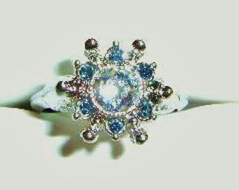"""Vintage 1974 AVON Ring """" STARSONG """" - Silver-toned Rhinestones with Blue in Flower Shape. Adjustable size and signed on inside of ring."""