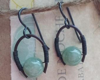 Beautiful high-quality Jade gemstone orbs suspended between dark annealed steel wire.