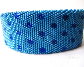 crocheted bracelet from small, light blue glass beads with flower pattern in dark blue.