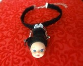 Creepy gothic doll head choker with contrasting white ribbon