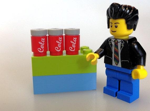 Cola Custom printed on a 1x1 round lego brick.