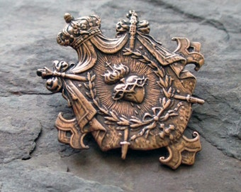 bronze shield charm or pendant medal with crown, sacred heart and swords jewelry finding