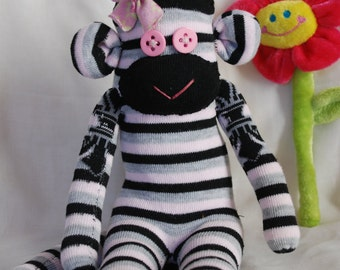 sock monkey, stuffed animal - grey, pink and black stripes with a pink flower on the head