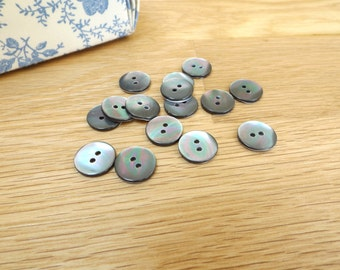 A pack of 6 circular, shell buttons, 15mm. Smokey grey in colour