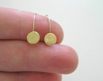 Small brass discs and sterling silver hoop earrings. Minimalist and modern everyday wear.