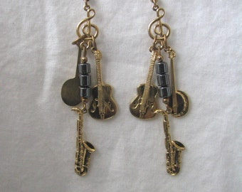 Gold tone vintage dangle hook earrings with music symbols guitar sax banjo