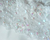 White bridal garter in stretch lace embellished with beads and iridescent sequins.