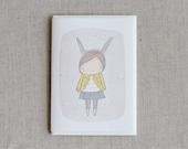 "Greeting Card -Bunny Girl Yellow Coat -  C6 greeting card 11w x 15.5 h cm (4.4x6.1"")."