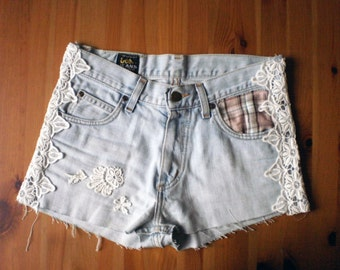 Upcycled jean shorts appliqué lace decoration.