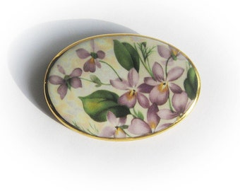 Lovely porcelain brooch with hand painted violets and leaves on an off~white porcelain cabochon with gold trim.