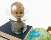 Creepy doll head mounted bobble head style in old glass bulb baby space oddity