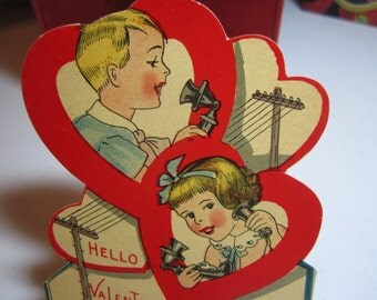 Adorable unused 1930's die cut valentine card showing a girl and boy speaking on old fashioned telephones