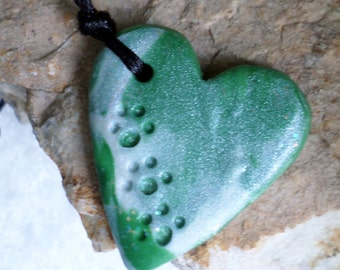 Paw Prints for Sam! Heart pendant handmade from polymer clay in swirled green and pearl.