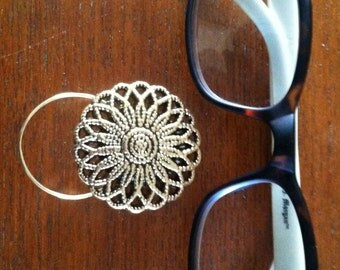 The mattie gold tone flower magnetic eyeglass holder is a pretty and practical way to keep track of your glasses.