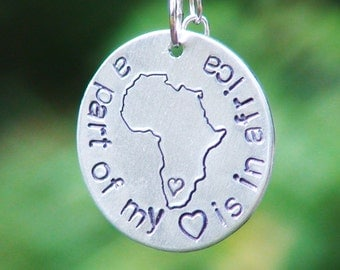 "Hand Stamped Aluminum Necklace stamped with Africa and ""A part of my (heart) is in Africa"" with Ugandan rolled bead"