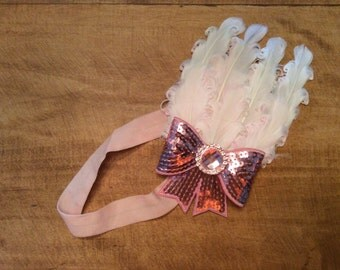 Pink headband with attached white feathers and pink sequin bow.