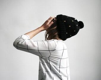 chapeau à la main couleur noir mignon avec des boucles d'oreilles en forme de coeur doré et pom pom de 100 % laine