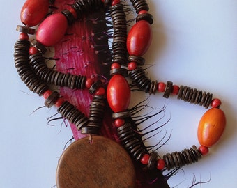 THE GERIBA NECKLACE - necklace.small espresso brown wood ships. small red beads.red & pink barrel-shaped wood pebbles. wood plate pendant.