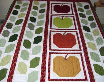 This is a large quilt that would be good for lap or table. It is machine pieced and hand quilted in traditional fall colors.Leaves and apple