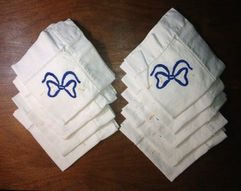 9 White linen napkins with blue bow and yellow accents
