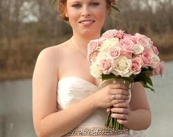 Radiant rhinestone and pearl bridal sash shown on blush velvet