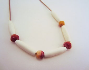 Bone necklace. Beaded necklace. Tan leather cord. Raspberry red beads. Long, smooth tube beads. Simple.