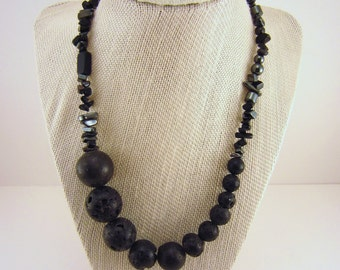 Black beaded necklace with ascending-sized beads. Round, pockmarked beads, smooth and shiny chips. Short extender. Ebony, slate necklace.