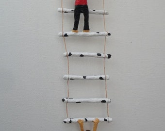 Boys on rope ladder sculpture