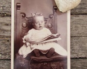 Odd Victorian cabinet card photograph of baby girl in glasses reading the newspaper