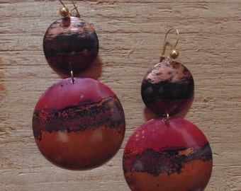 Copper colored earrings in focus