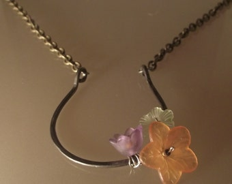 Silver horseshoe and wildflower necklace.