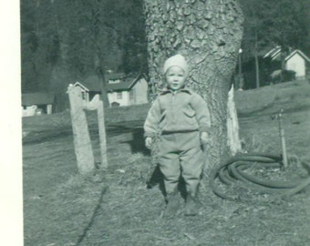 All bundled up Toddler Boy Standing Outside in Wool Coat Pants Hat by Tree Farm Town 1920s Vintage Black White Photo Photograph