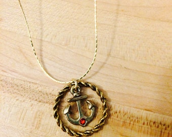 Gold anchor necklace with red gem